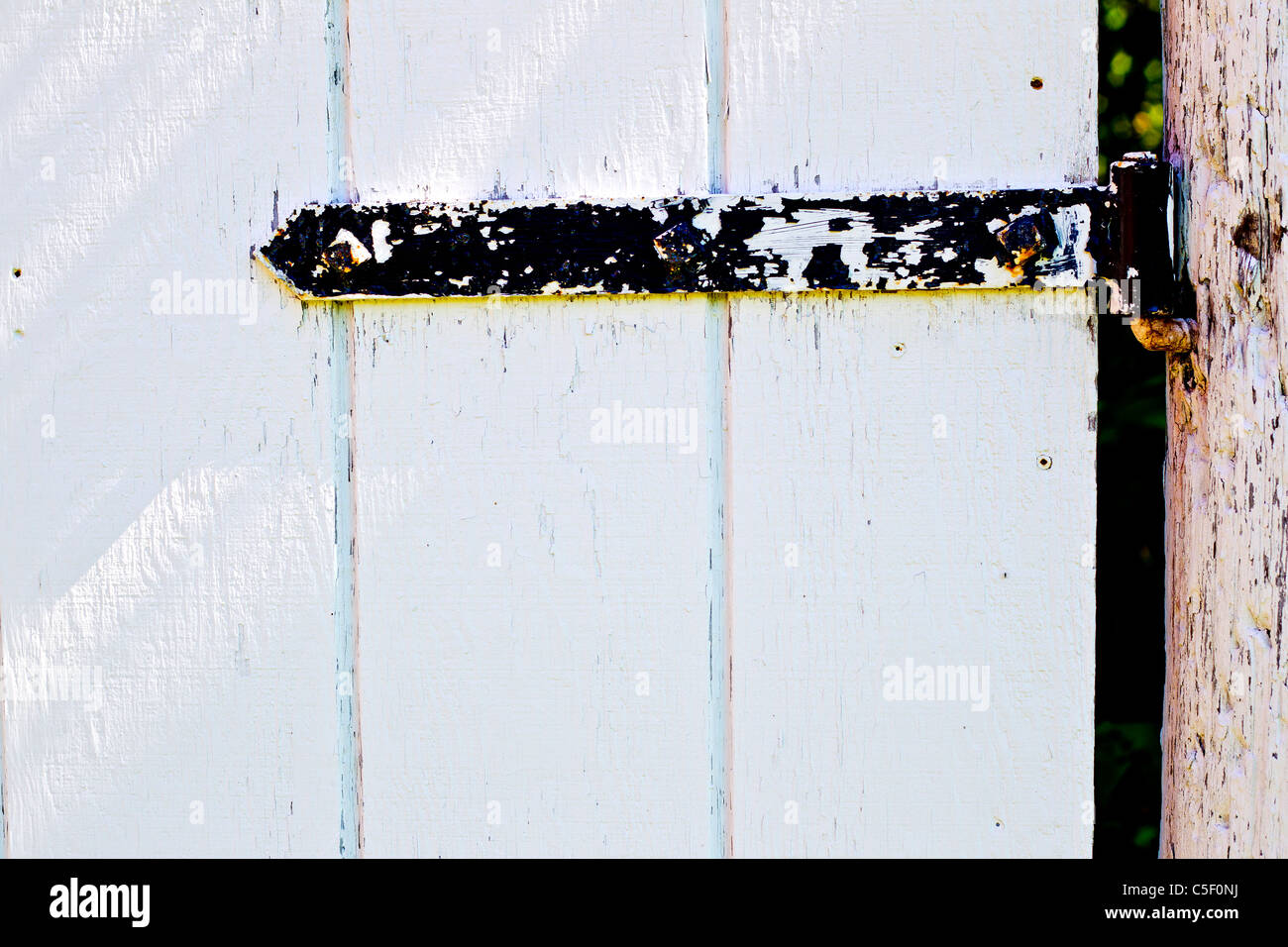 eine schwarze tür scharnier auf einer hölzernen weißen tor stockfoto