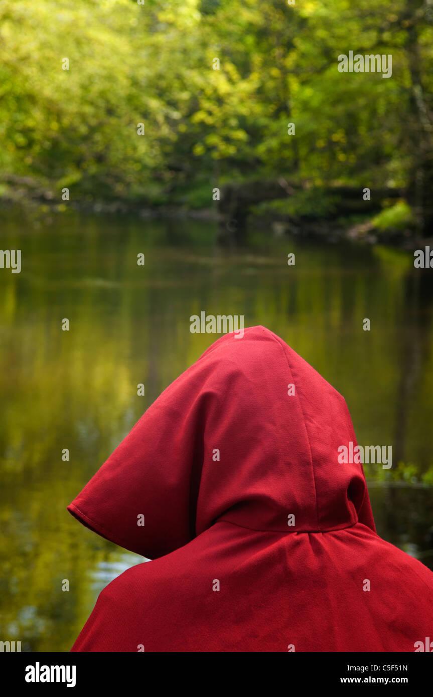 Geheimnisvolle Person im roten Umhang im Wald am See Stockbild