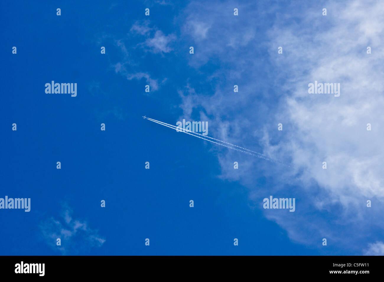 Jet-Kondensstreifen (Kondensstreifen) in blauer Himmel mit Wolken Stockbild
