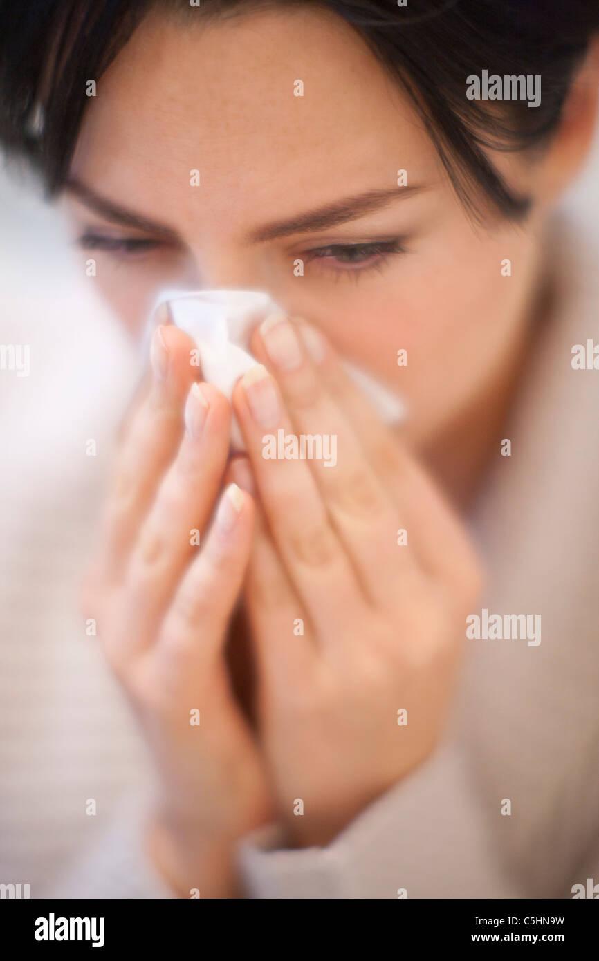 Frau, die ihre Nase weht Stockbild