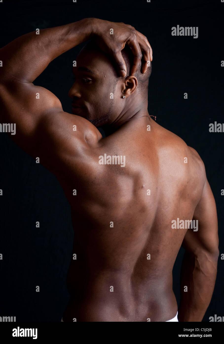 Muskulöser afroamerikanische Mann zeigt seine Muskeln von Rücken und ...