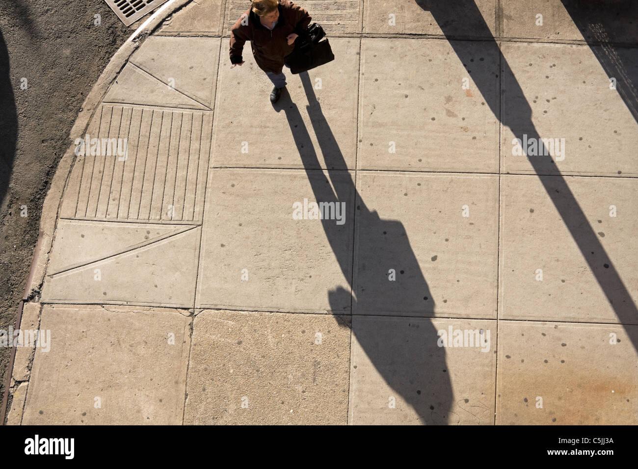 Eine Frau in New York City wirft einen langen Schatten am späten Nachmittag. Stockbild