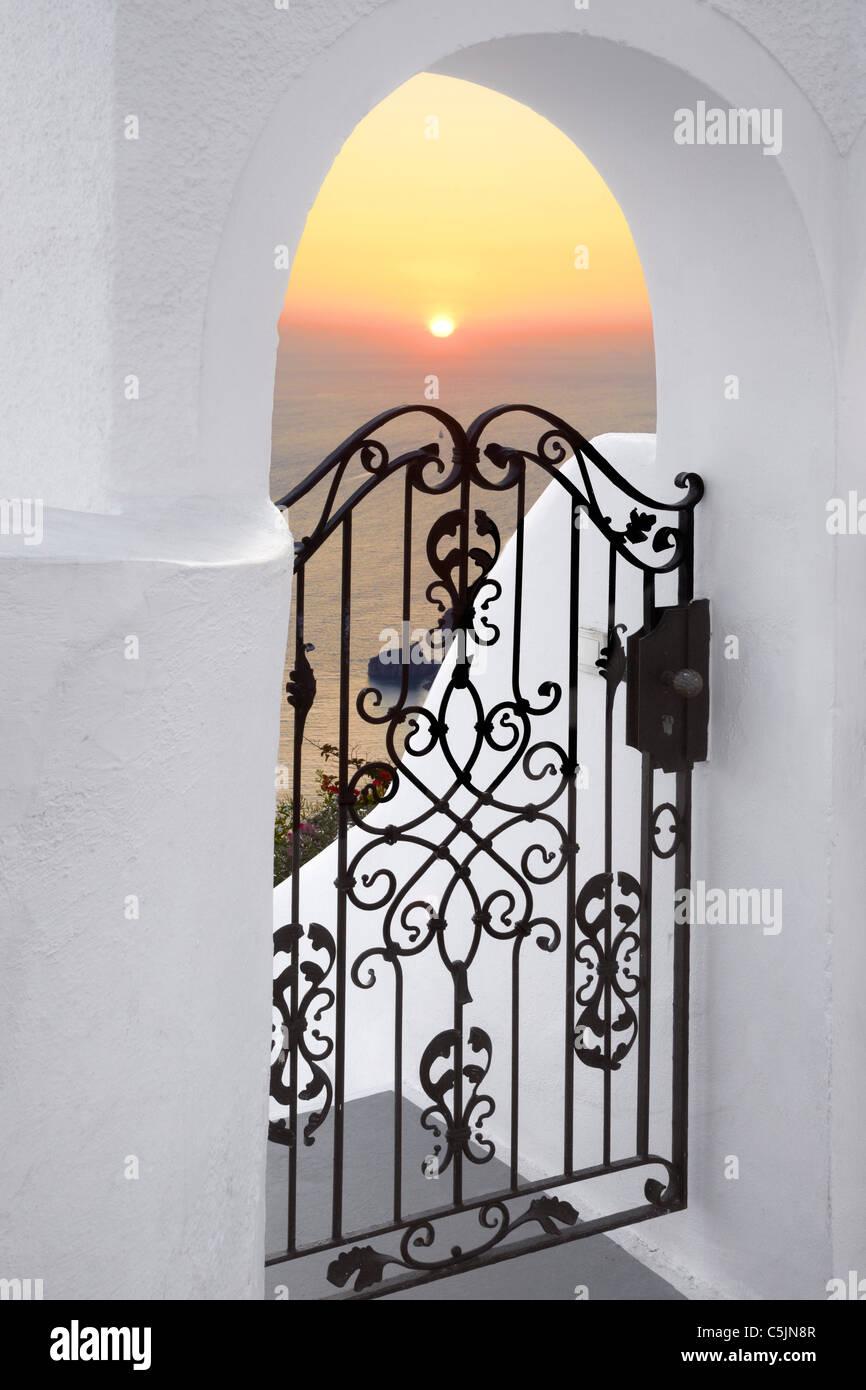 Thira (Kapital Stadt von Santorini) - Tür mit weißen Wänden und den Sonnenuntergang im Hintergrund, Stockbild