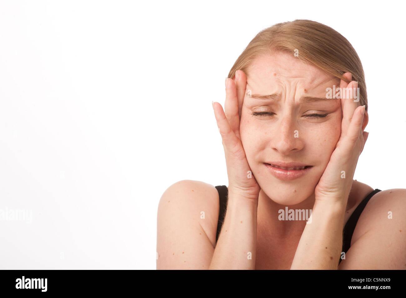 eine junge kaukasischen Frau mit Kopfschmerzen Stirn reiben zur Linderung der Schmerzen, UK Stockbild