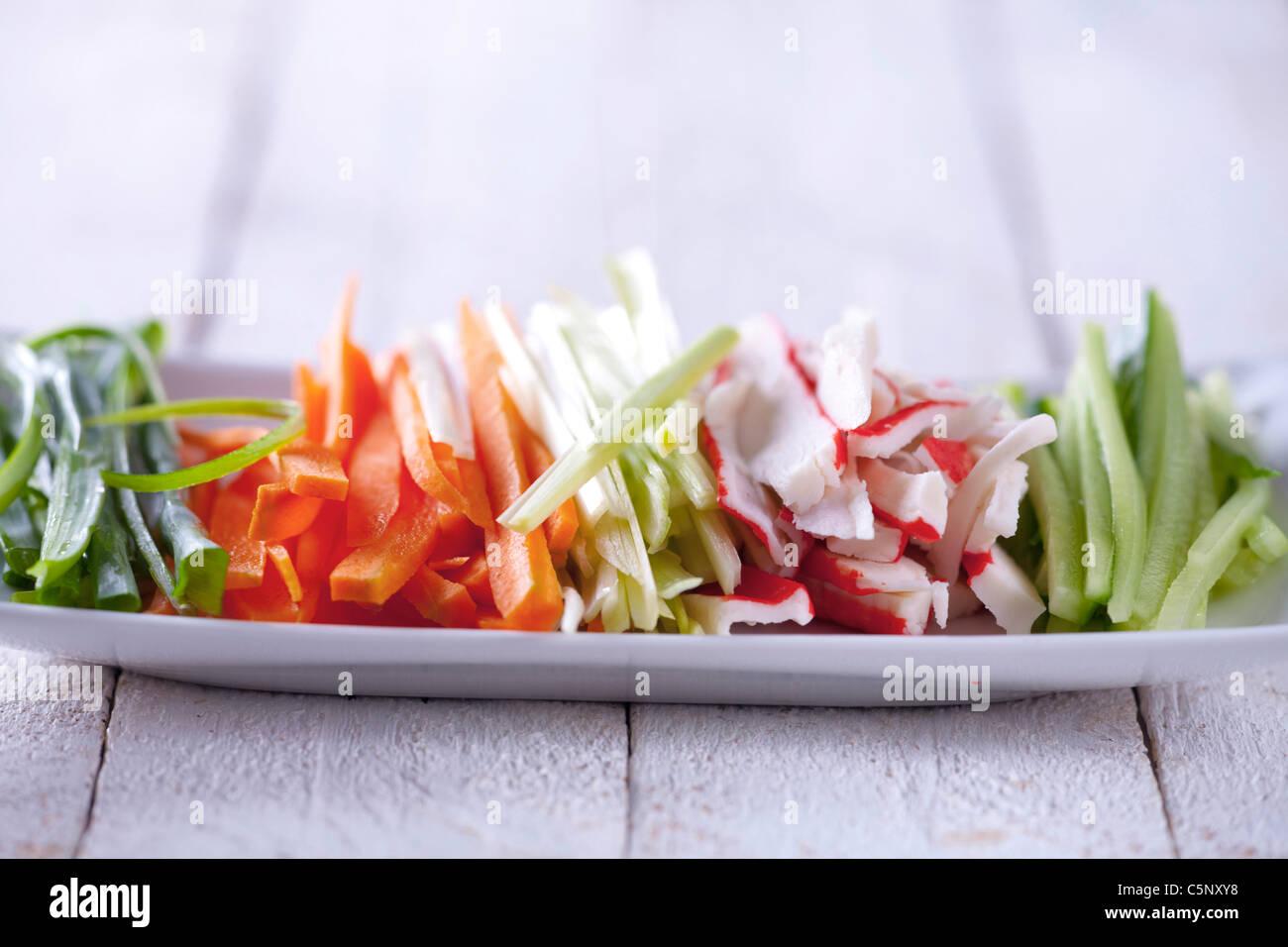 Streifen von Schnittlauch, Karotten, Lauch, Surimi und Gurke Stockbild
