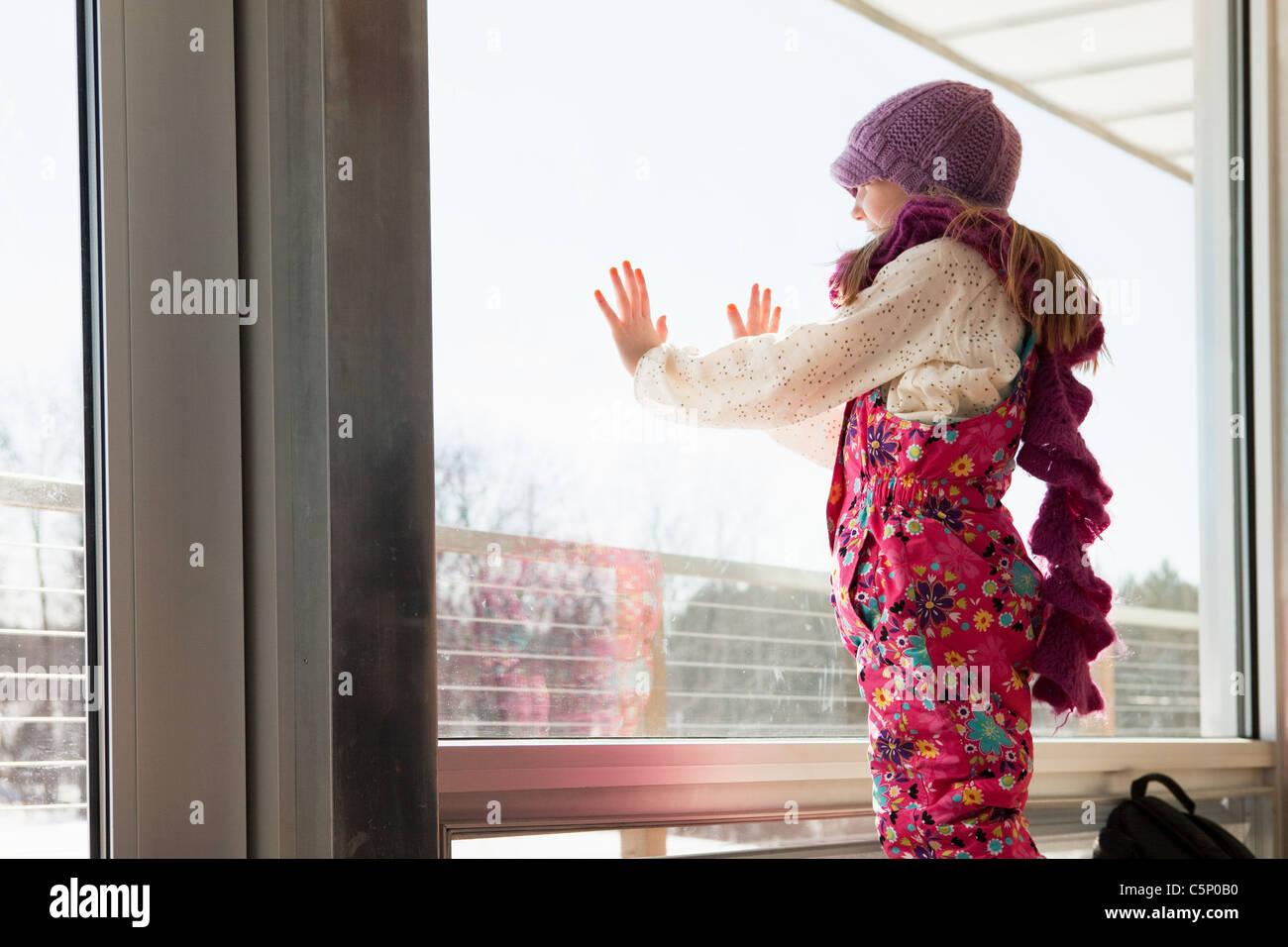 Mädchen auf der Suche durch Fenster Stockbild