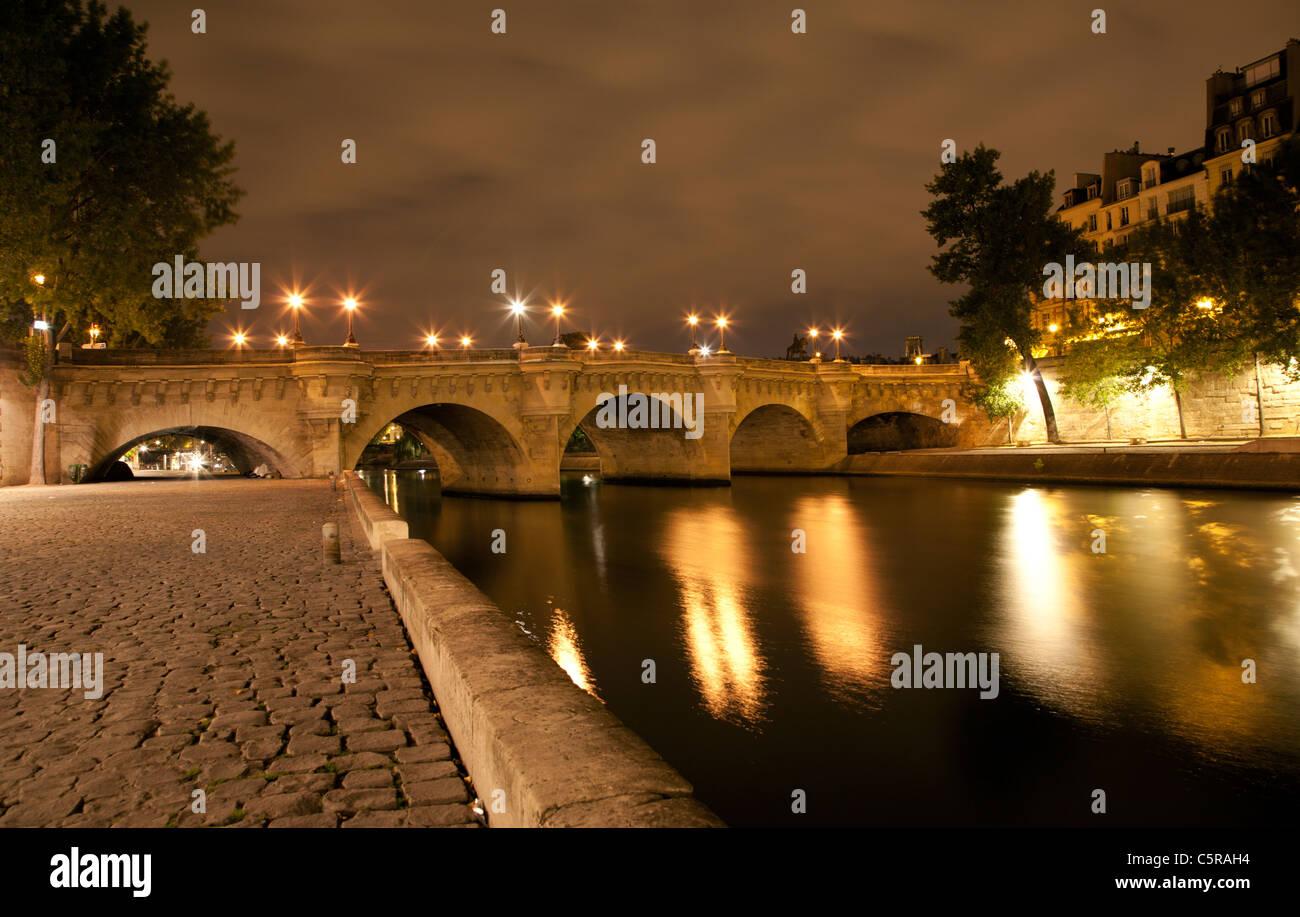 Paris - Ponte Nuef am Flussufer in Nacht Stockbild
