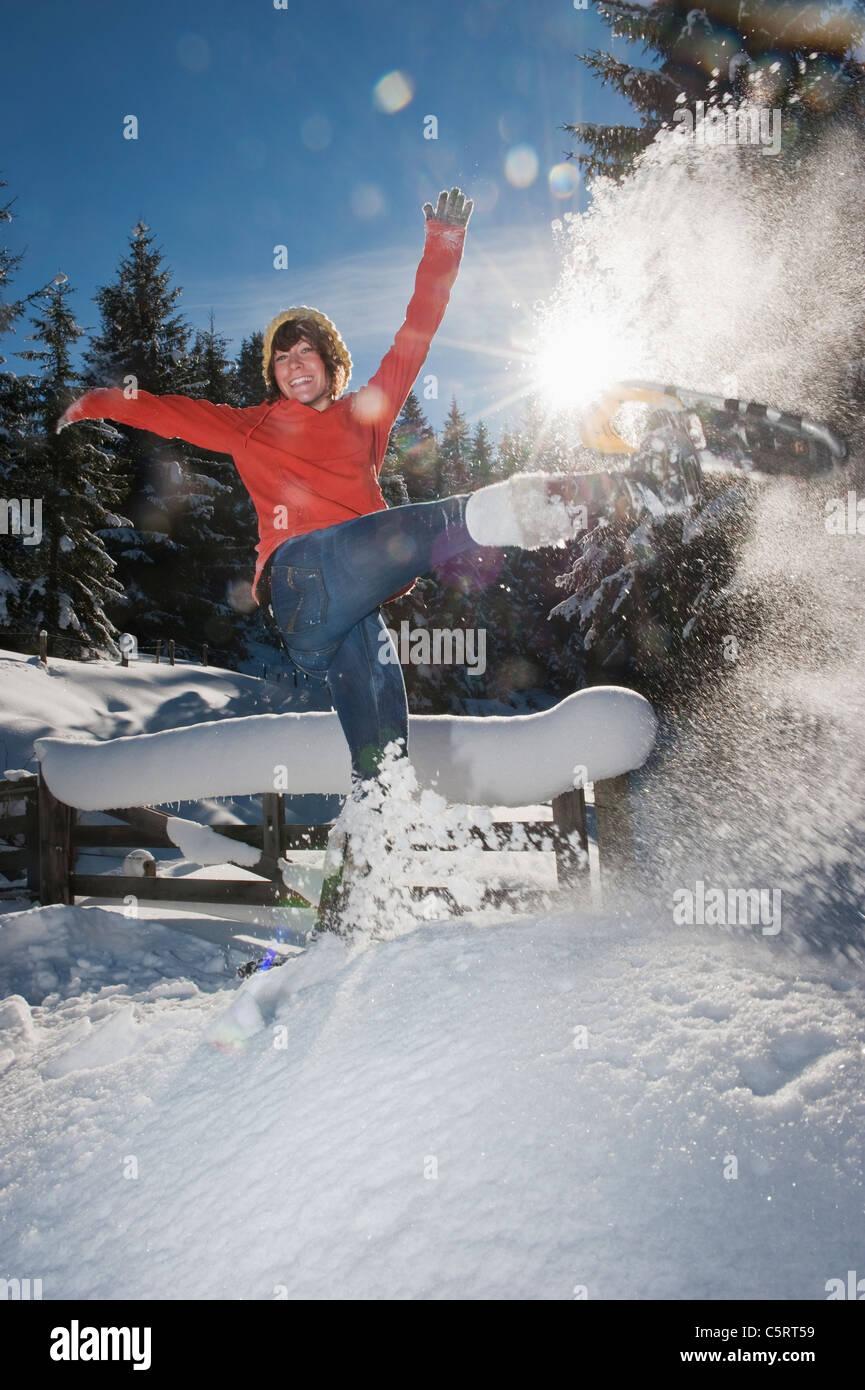 Österreich, Salzburger Land, Flachau, junge Frau mit Schneeschuhen springen im Schnee Stockbild