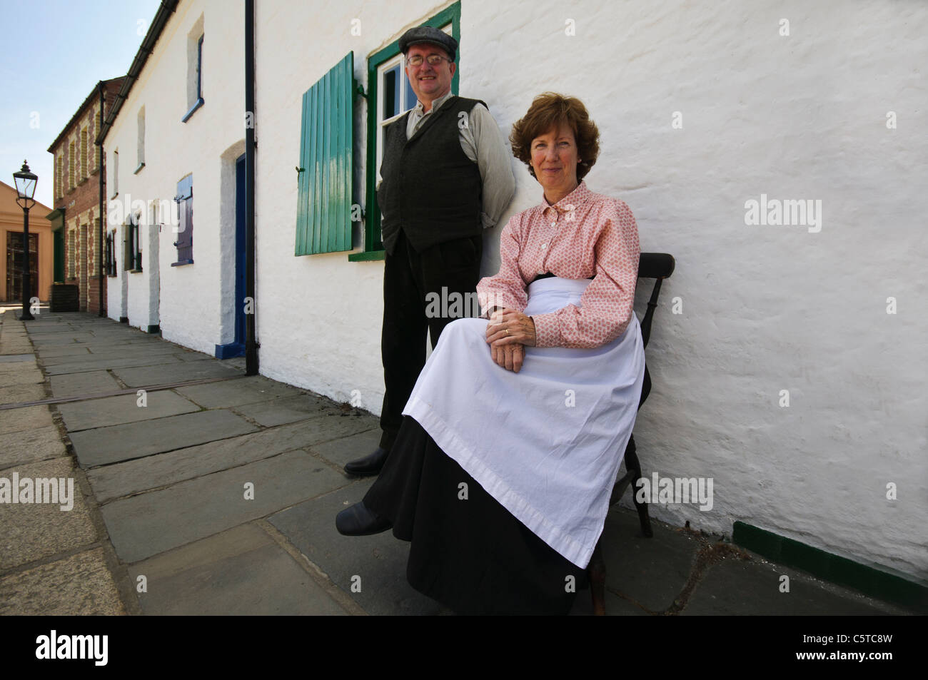 Mann und Frau im viktorianischen Kleid sitzen auf dem Fußweg vor ihrem Haus im Ulster Folk Park Museum Stockfoto