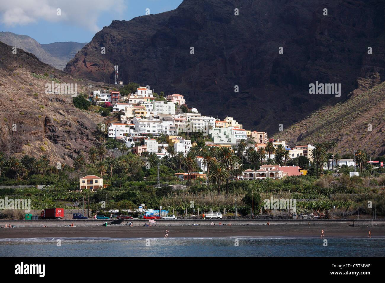 Spanien, Kanarische Inseln, La Gomera, Valle Gran Rey, La Calera, Touristen am Strand mit Bergen Stockbild