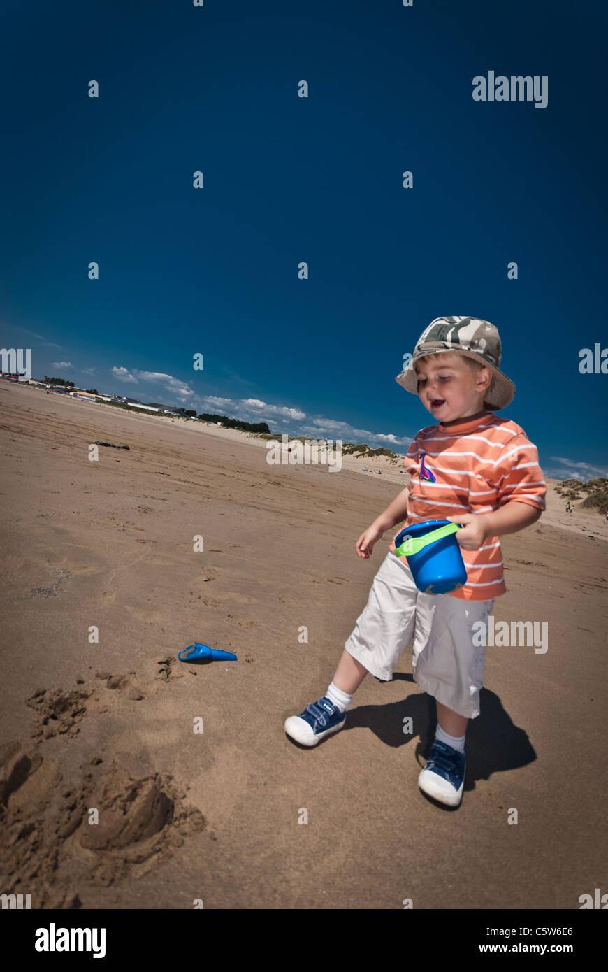 ein kleiner Junge macht Sandburgen an einem Sandstrand an einem wolkenlosen Sommertag Stockbild