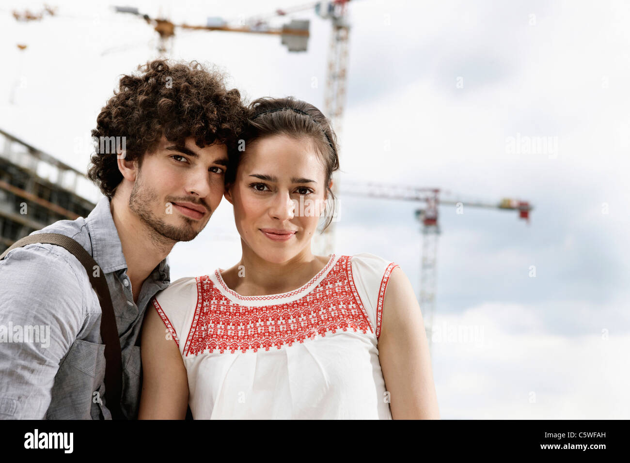 Deutschland, Berlin, junges Paar vor Neubau, Kräne im Hintergrund Stockbild
