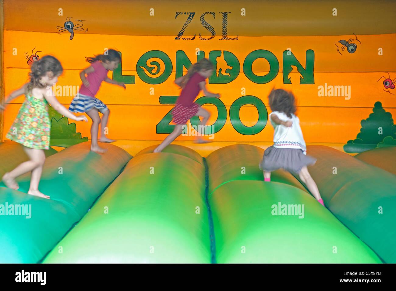 Vier kleine Mädchen hüpfen auf eine aufblasbare Hüpfburg im Londoner Zoo. Stockbild