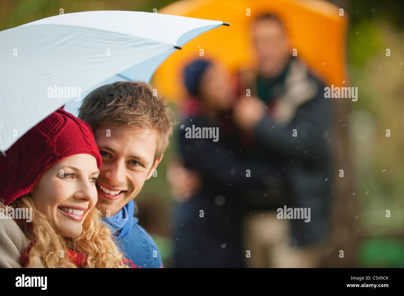 Deutschland, Bayern, englischer Garten, vier Personen im Biergarten, holding, Regenschirm, Lächeln, Porträt, Stockbild