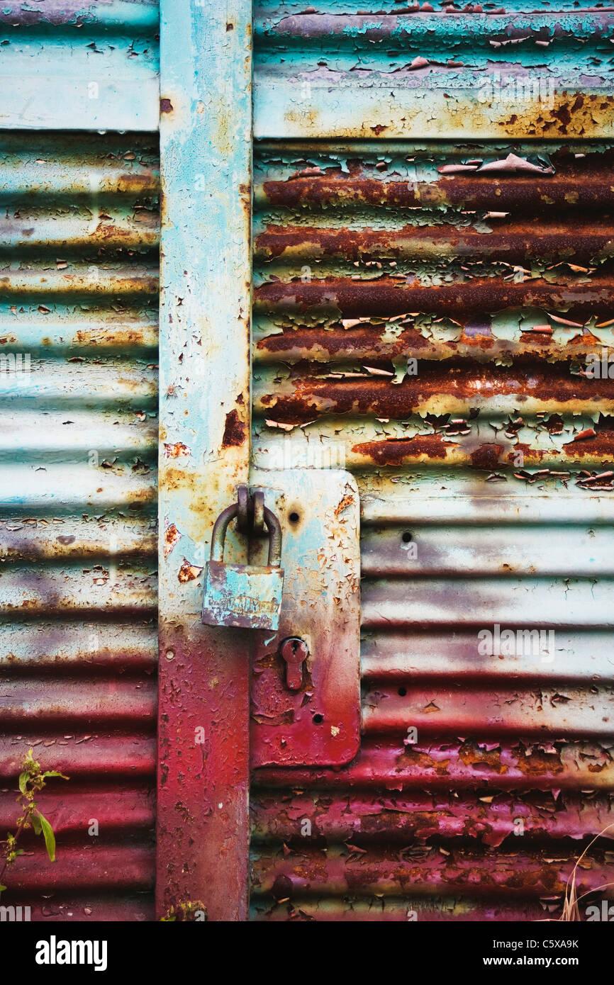 Metall-Eingangstür mit rostigen Vorhängeschloss Stockbild