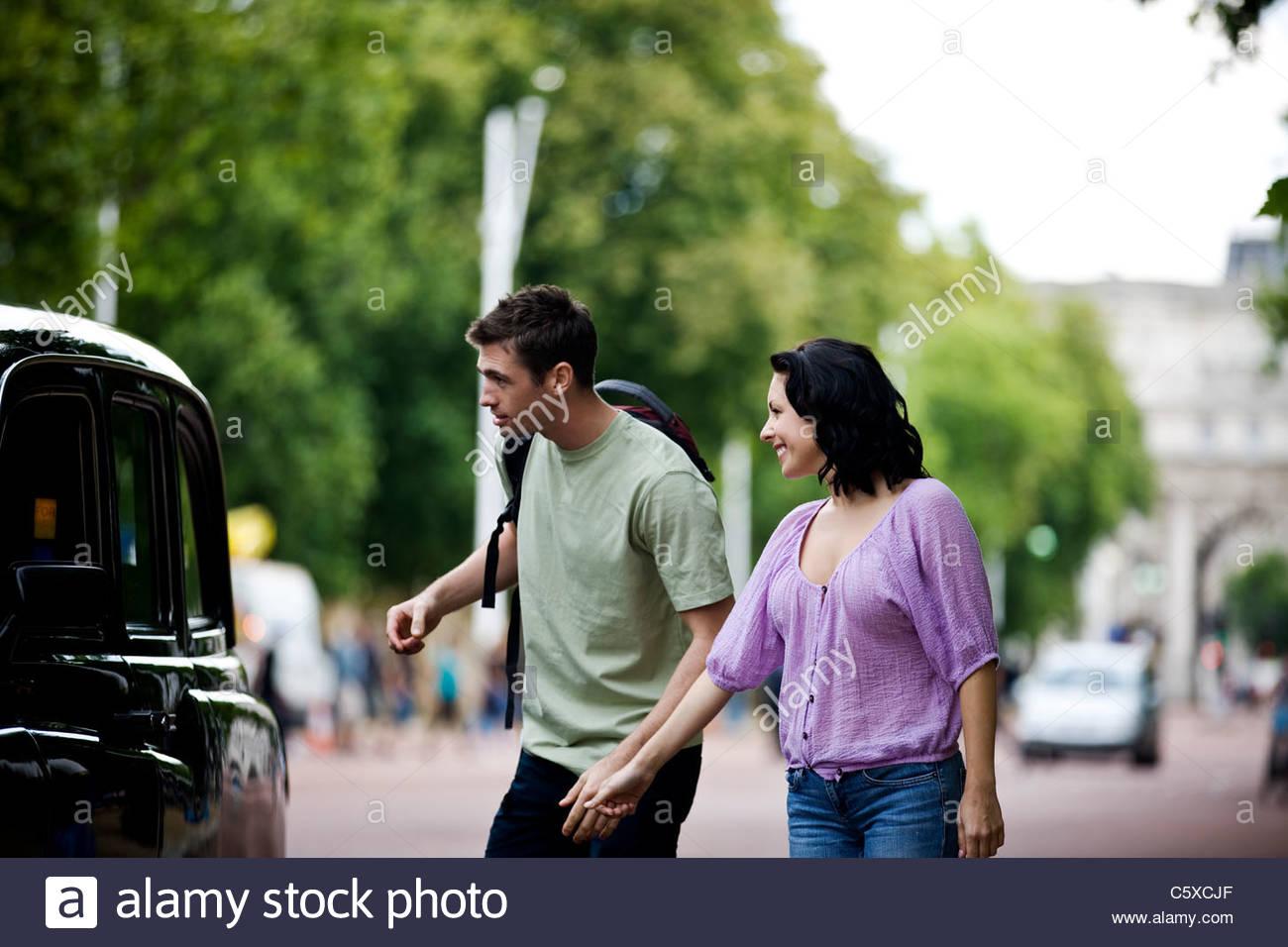 Ein junges Paar im Gespräch mit einem Taxi-Fahrer Stockbild