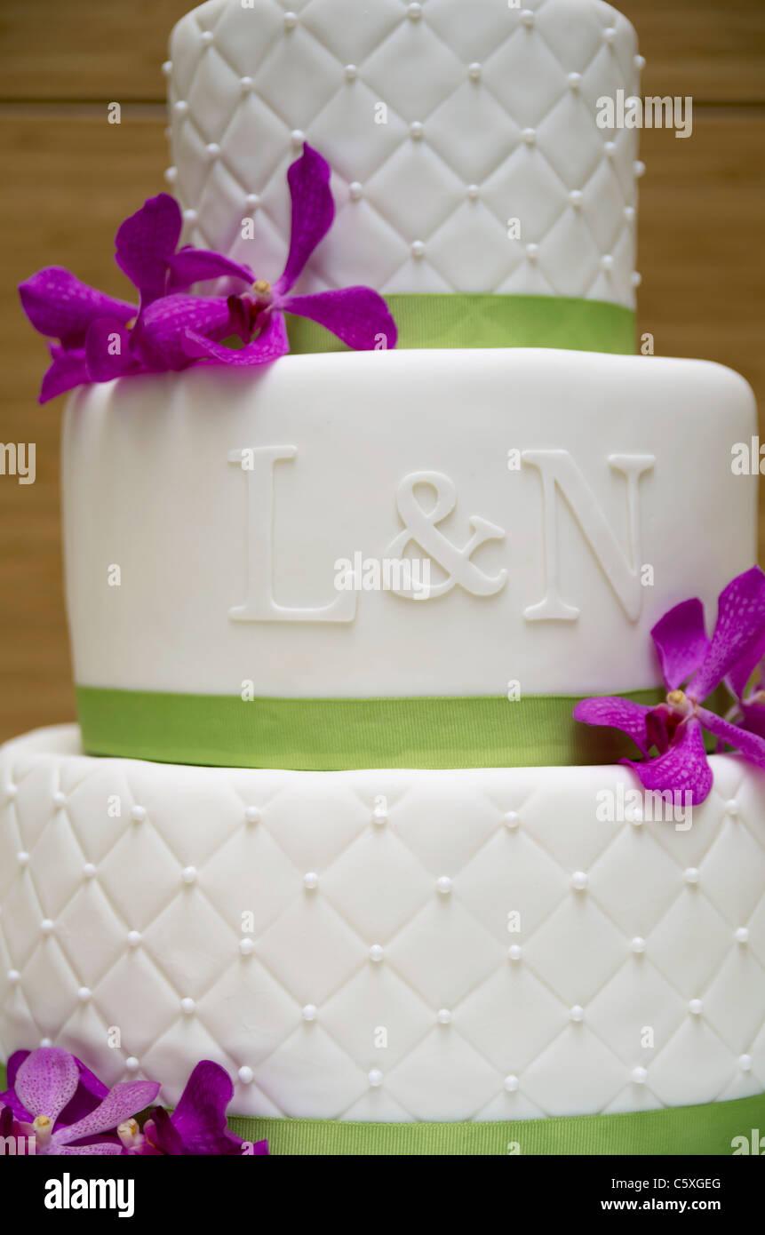 Eine Hochzeitstorte Mit Lila Bluten Weisse Ganache Und Grunband Und