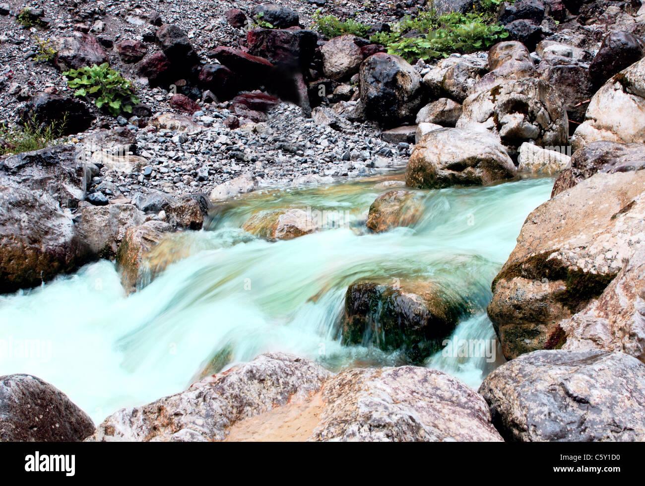 schnell klare Bergfluss zwischen großen Steinen Stockbild