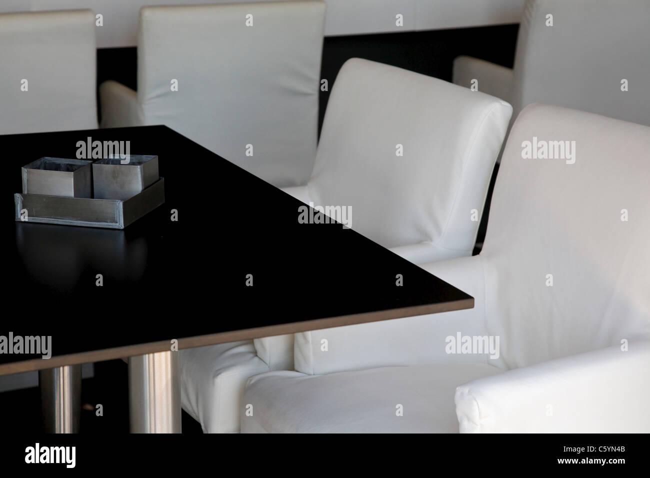 Einige bequeme aussehende Stühle in einer Bar eine leere schwarze Tabelle Stockbild