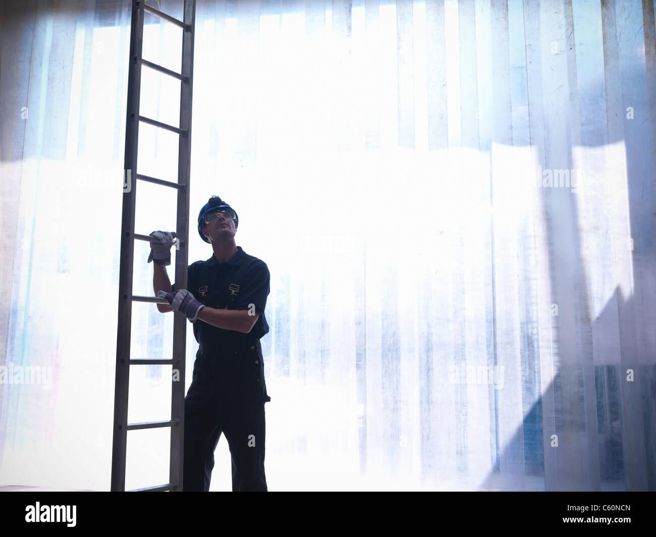 Arbeiter halten Leiter Stockbild