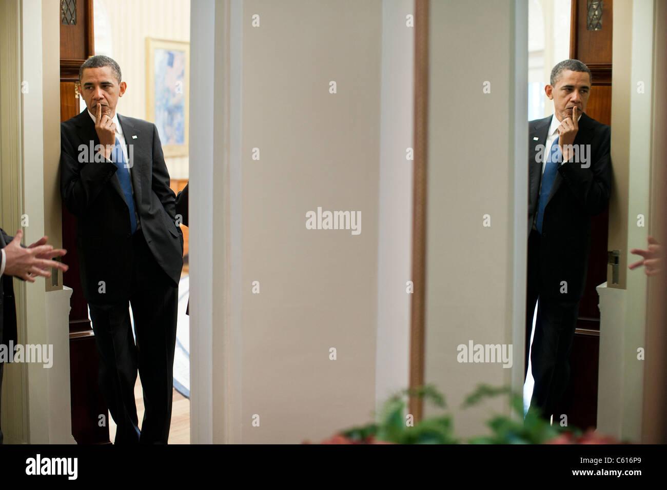 Präsident Obama spiegelt sich in einem Spiegel, da er mit Bill Daley links und VP Joe Biden in der Tür Stockbild