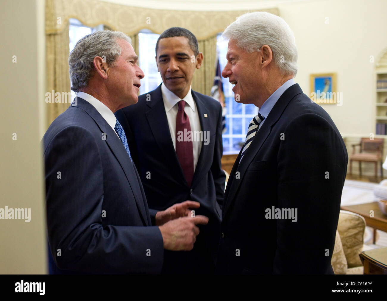 Präsident Obama hört ein Gespräch zwischen ehemaligen Präsidenten Bill Clinton und Bush nach Stockbild