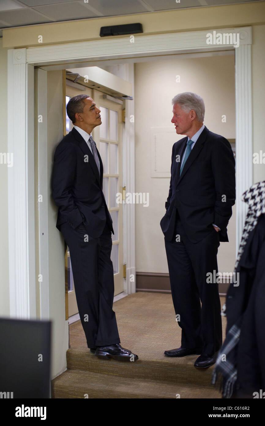 Präsident Obama spricht mit dem ehemaligen Präsident Clinton vor dem Treffen mit Journalisten im Weißen Stockbild