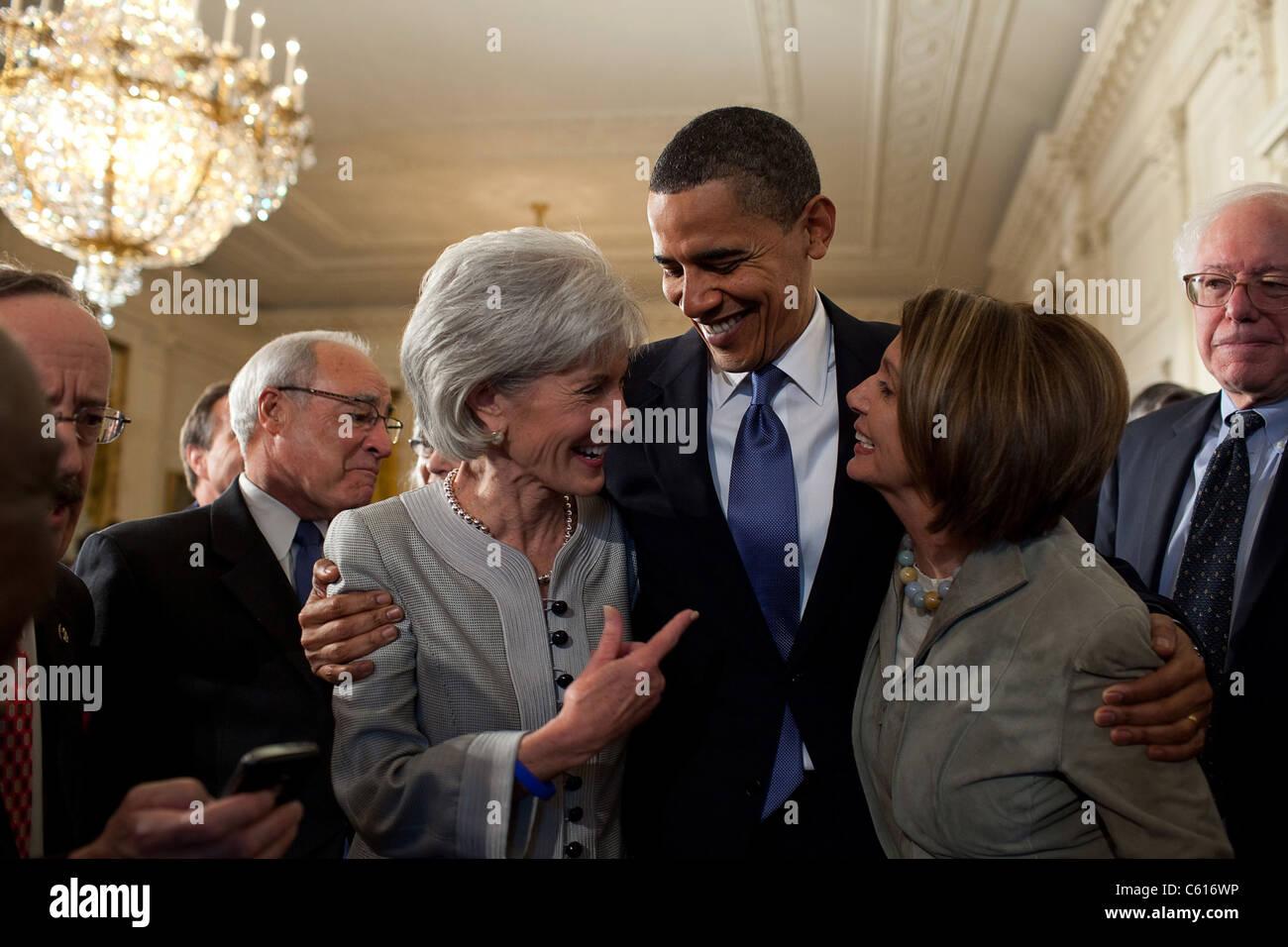 Präsident Obama umarmt Health Secretary Kathleen Sebelius links und House Speaker Nancy Pelosi nach Unterzeichnung Stockbild