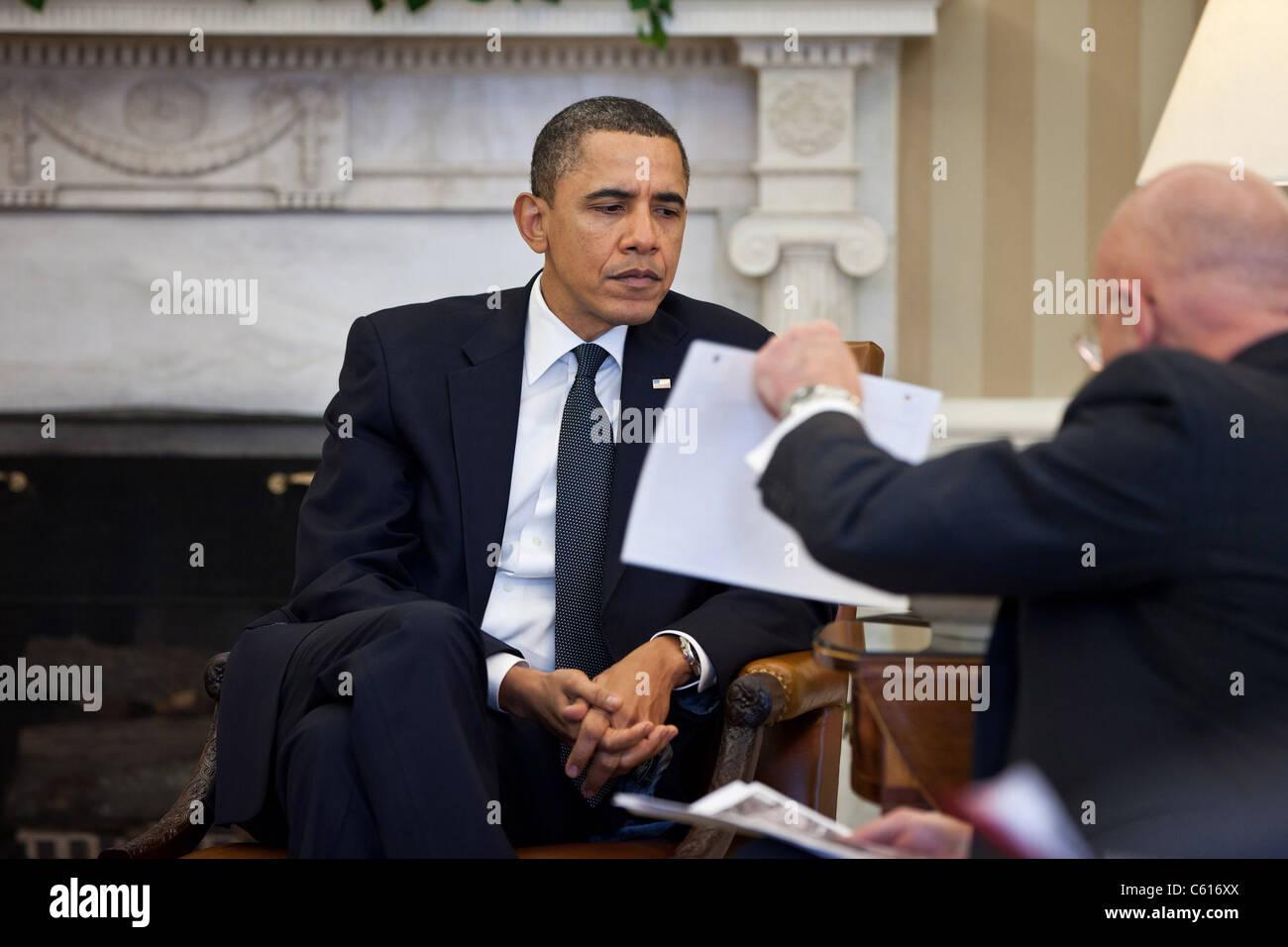 Präsident Obama Studien ein Dokument während der Präsidentschaftswahlen Daily Briefing im Oval Office Stockbild