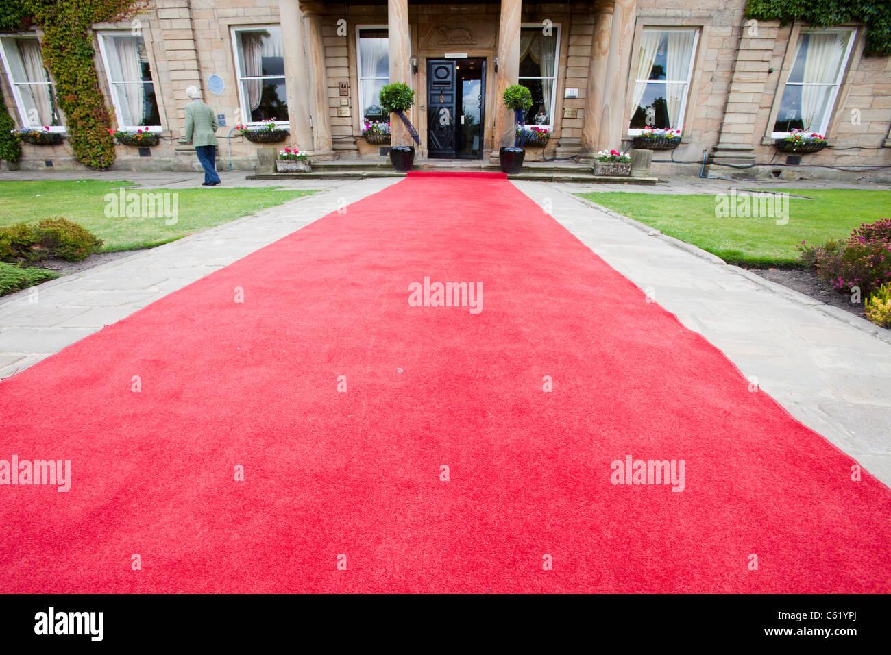 Ein roter Teppich führt in Richtung Walton Hall in der Nähe von Wakefield, Yorkshire, Großbritannien. Stockbild