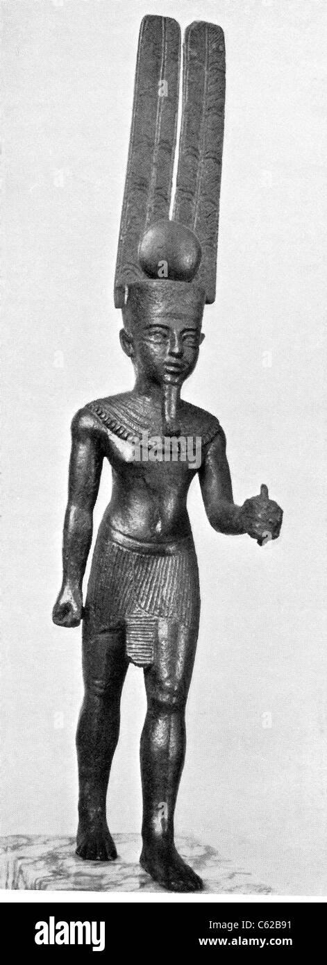 Dieser antike ägyptische Statue zeigt den Gott Amun-Re die Sonnenscheibe mit zwei großen Federn tragen. Stockbild