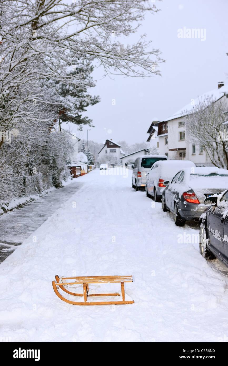 Schlitten und geparkte Autos im winter Stockbild