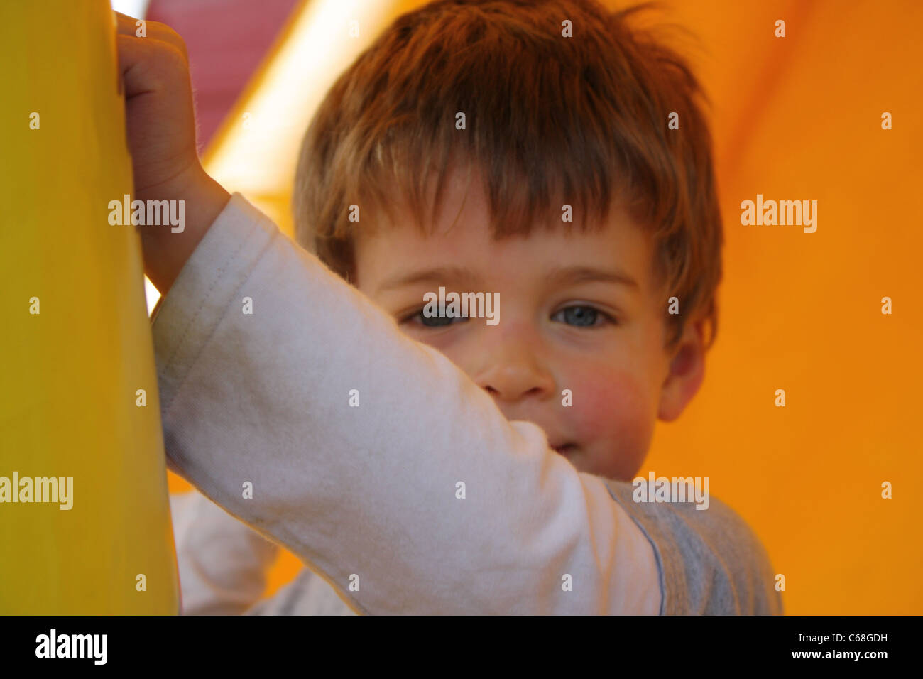 Junge, eine Pause auf einer Hüpfburg Stockbild