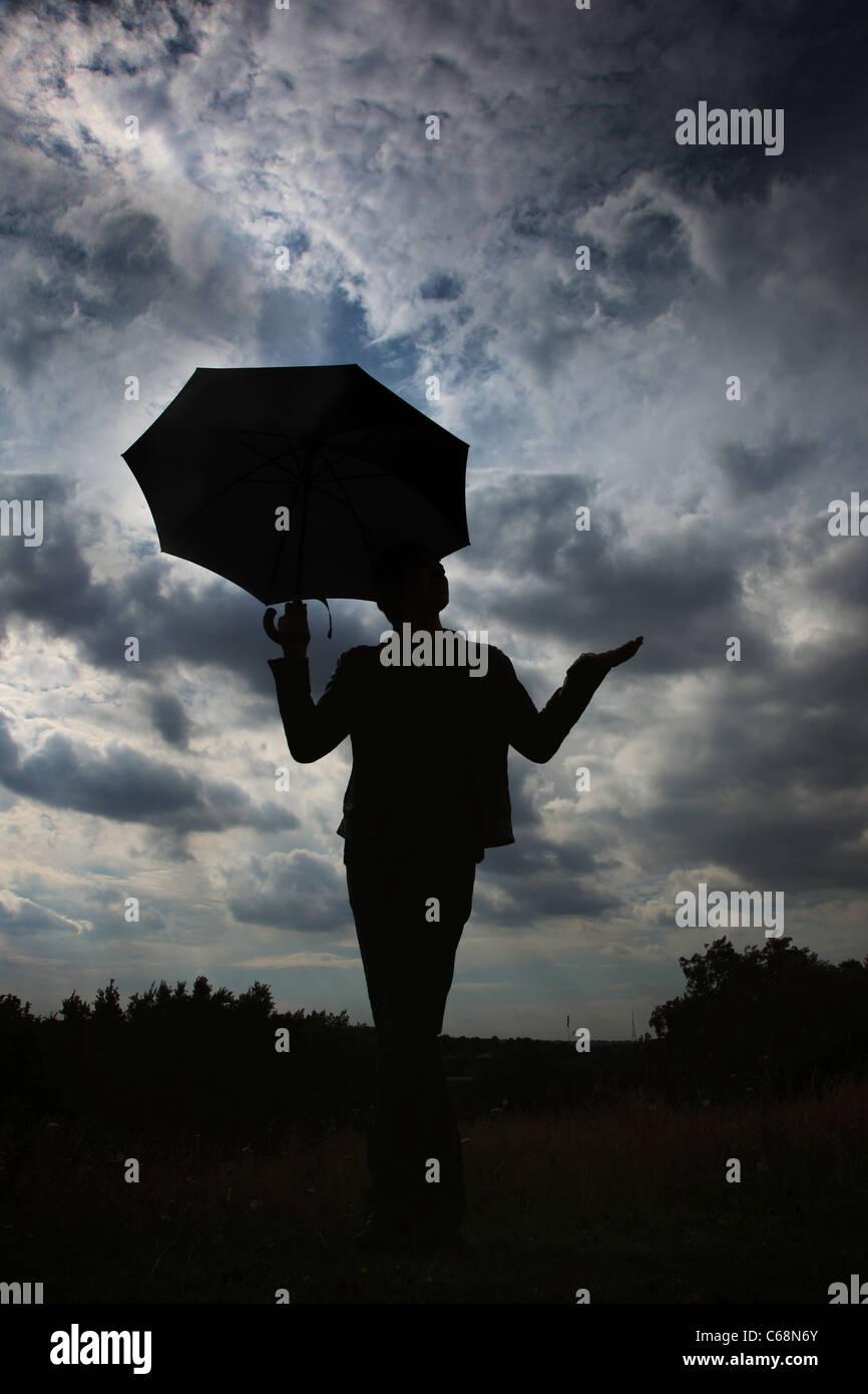Mann stand vor einem bewölkten Himmel, hand, Regen, Regenschirm halten gesucht. Stockbild