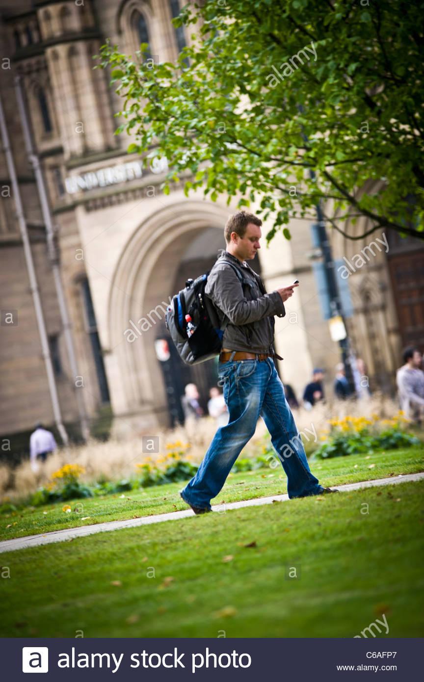 totale der Studenten zu Fuß auf Weg durch Rasenfläche auf Uni-campus Stockbild