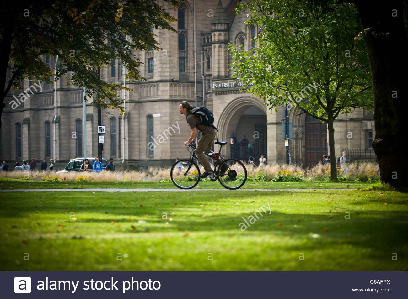 totale der weißen männlichen Studenten auf Fahrrad Radfahren auf Pfad zwischen Grünfläche am Stockbild