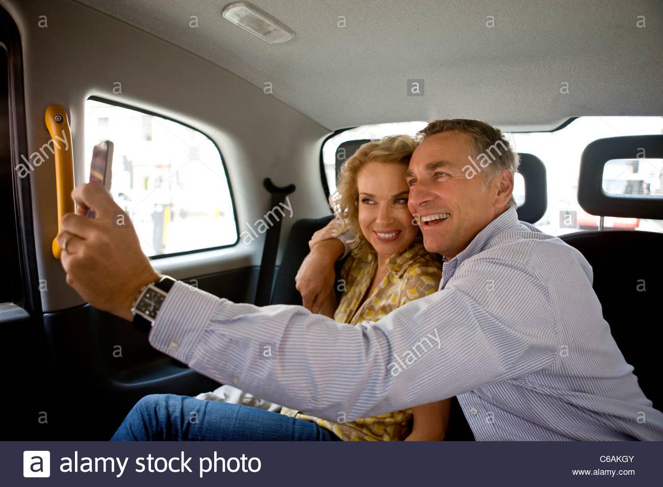 Ein paar mittleren Alters in einem London-Taxi, ein Foto von sich selbst Stockbild