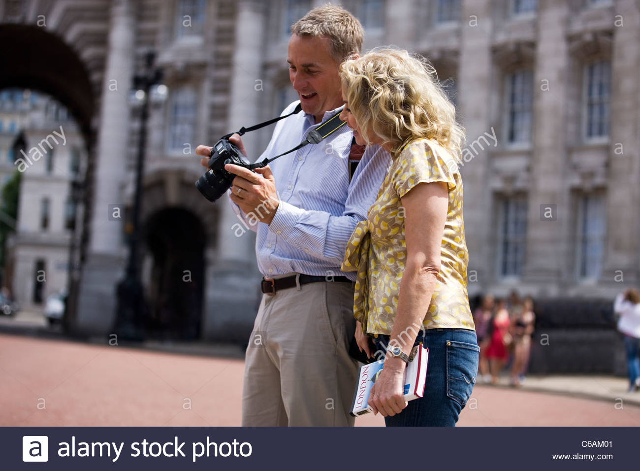 Ein paar mittleren Alters, betrachten von Fotos auf ihrer Kamera Stockbild