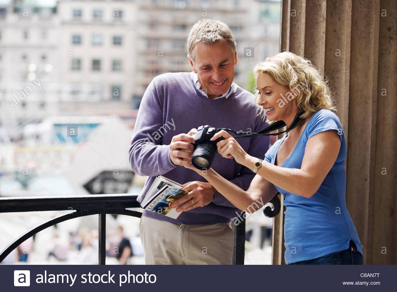 Ein paar mittleren Alters von Trafalgar Square stehen, betrachten von Fotos auf ihrer Kamera Stockbild