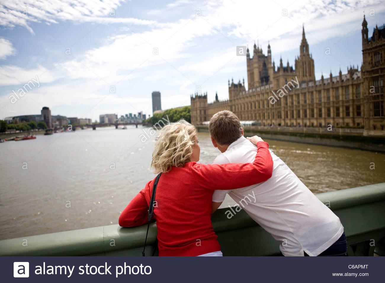 Ein paar mittleren Alters Stand in der Nähe der Houses of Parliament, Suche entlang der Themse Stockbild