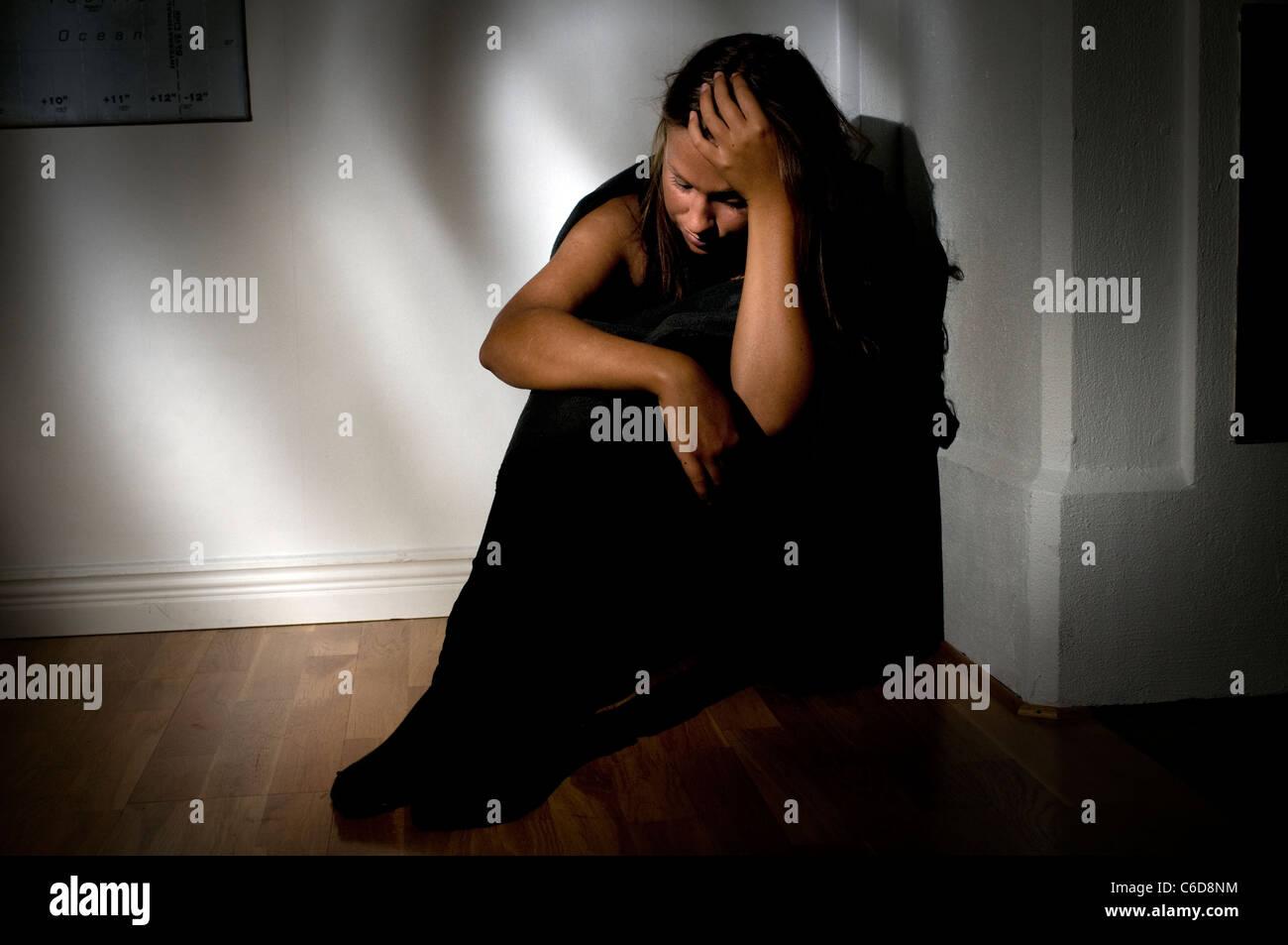 Junge Frau, die leiden, Depressionen oder Krankheit in abgedunkelten Raum Stockbild