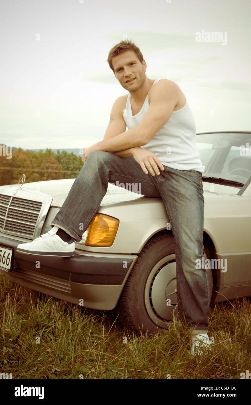 Mann mit Mercedes-Wagen in einem 80er Jahre look Stockbild