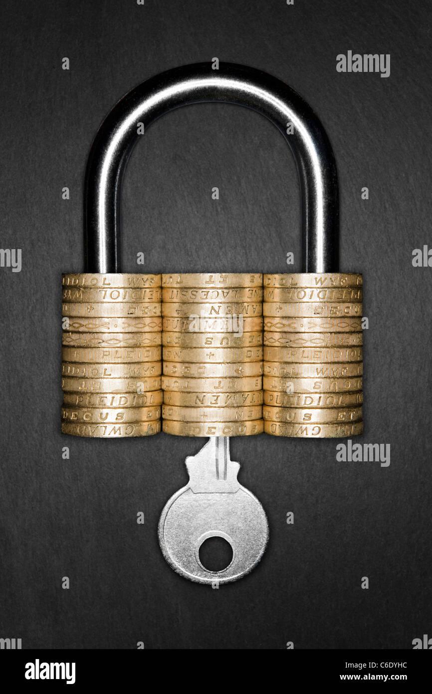 Konzept der finanziellen Sicherheit. Vorhängeschloss in Pfundmünzen hergestellt. Schlüssel in Vorhängeschloss eingesetzt Stockfoto