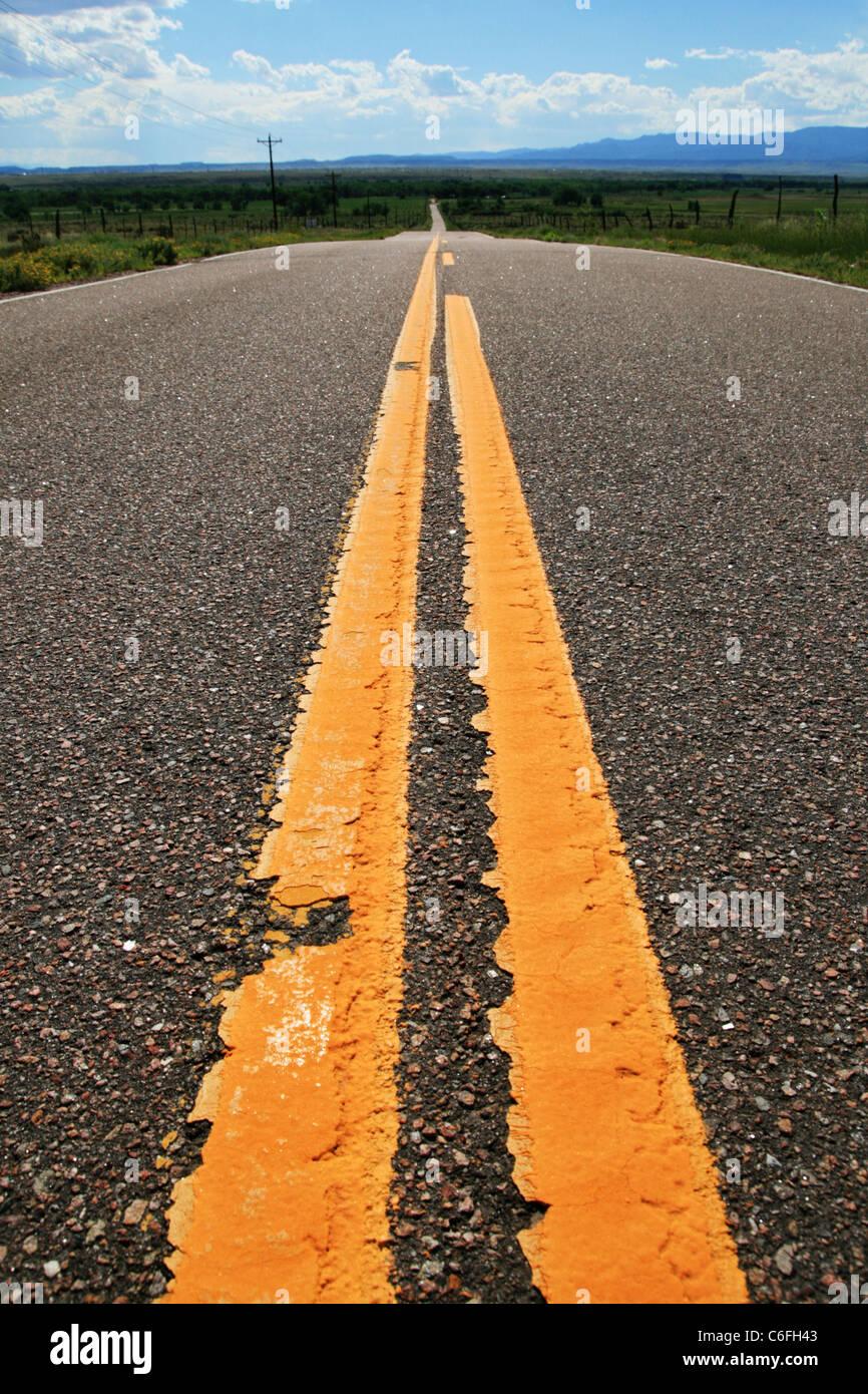 gelbe Linien auf einer Landstraße Überschrift in die Ferne Stockbild