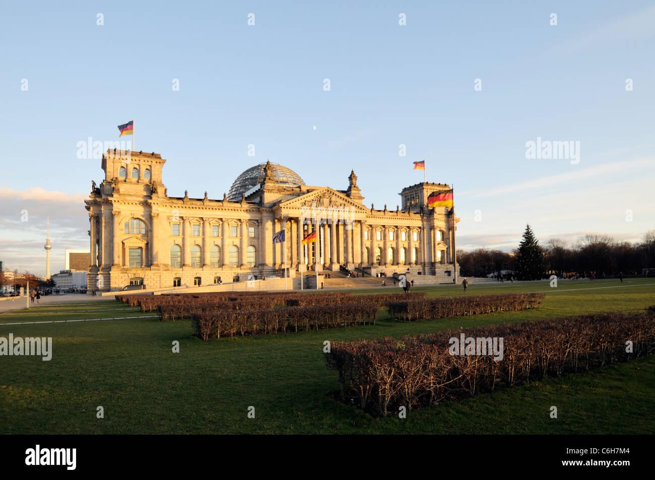 Warmen Abend Sonnenlicht beleuchtet den mächtigen Reichstag mit klaren, blauen Himmel und Fahnen. Stockbild