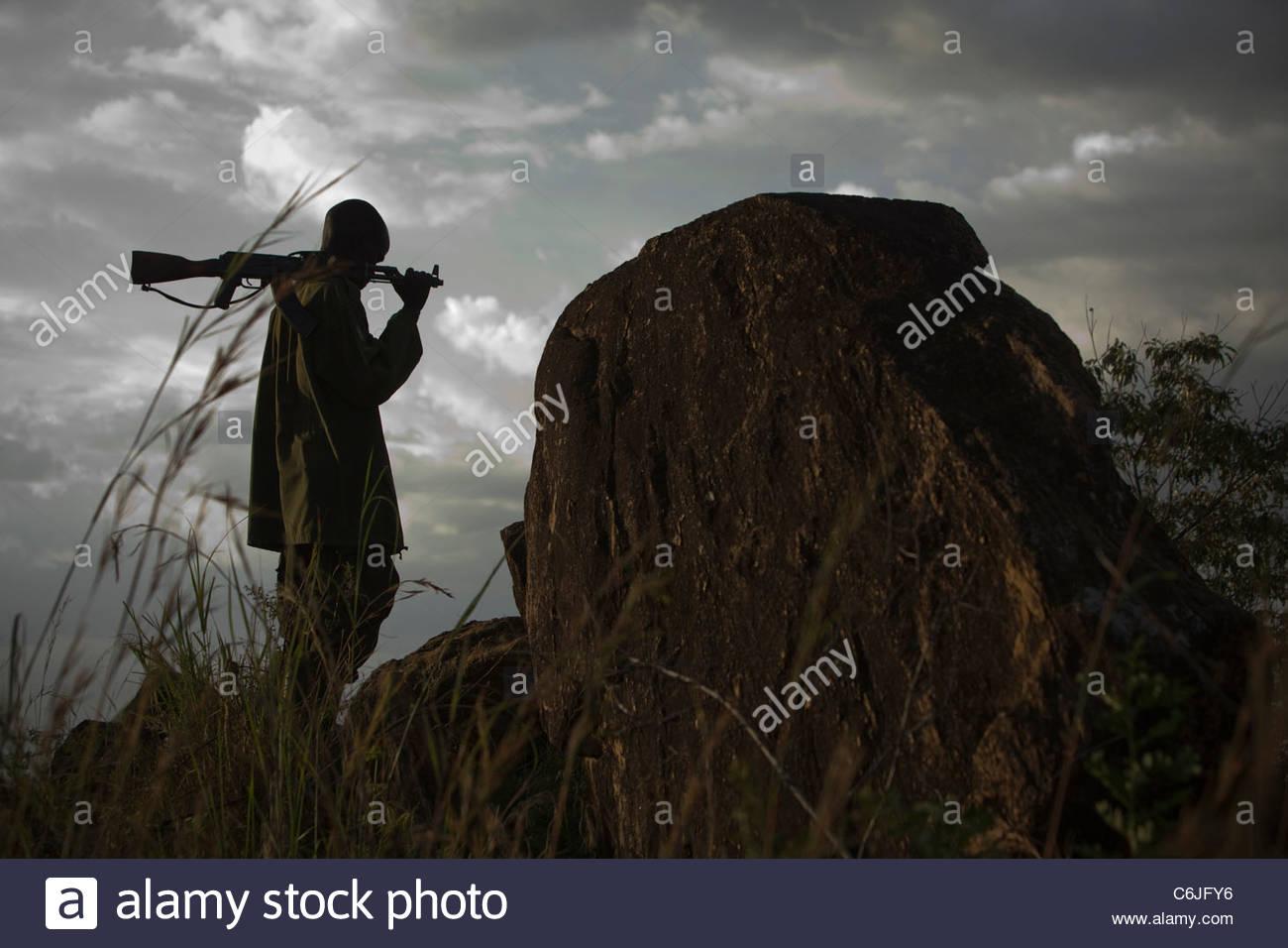 Mann mit einem Gewehr über seine Schulter stehen bei bewölktem Himmel Stockbild