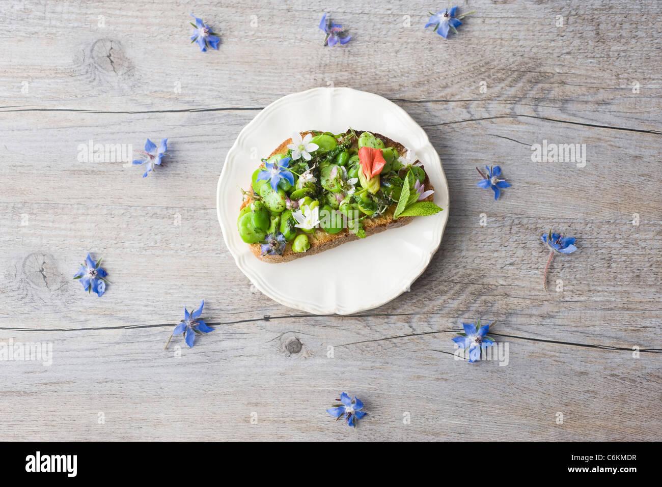Bohne und Kraut Tartines mit Wildblumen Stockfoto
