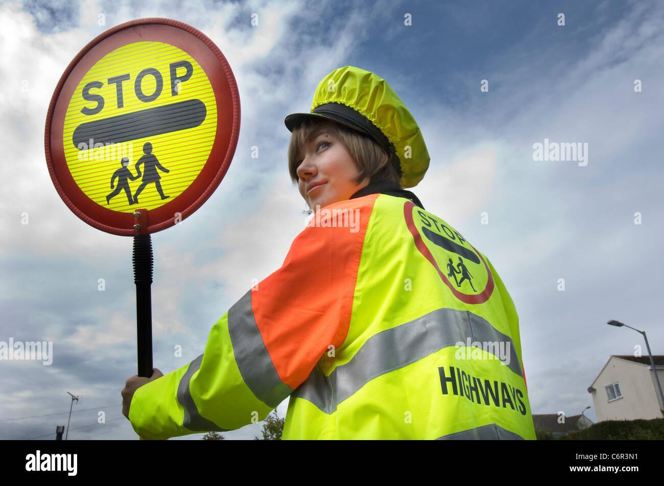 Ziemlich lächelnde Teenager Lutscher Dame an der Schule Kreuzung Wachposten in ländlichen Cornwall Stockbild