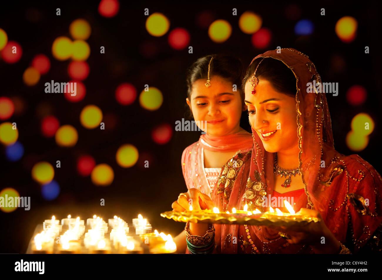 Mutter ein Tablett mit Diyas zu halten, während ihre Tochter blickt auf Stockbild