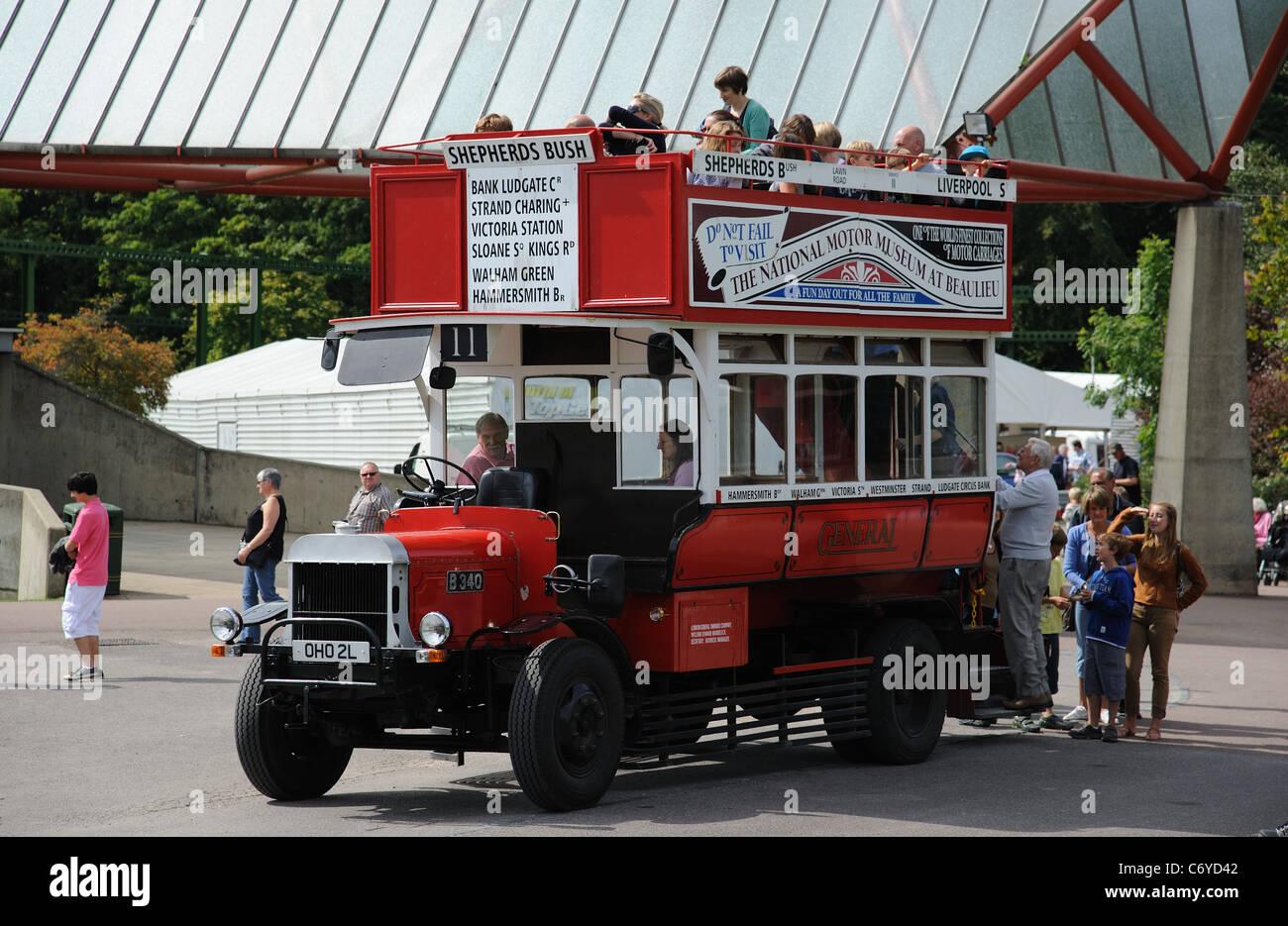 Oldtimer Bus Nummer 11 mit Passagieren einsteigen außerhalb der National Motor Museum in Beaulieu in Hampshire, Stockbild